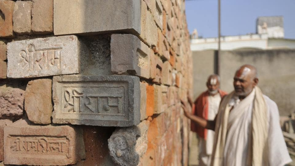 Devotees touch bricks with 'Shri Ram' embossed and engraved on them during a visit to the Ram Janm Bhoomi Nyas workshop at Karsevak Puram on the day of the Supreme Court verdict in the Ram Janmabhoomi Babri Masjid case, at Ayodhya, Uttar Pradesh.