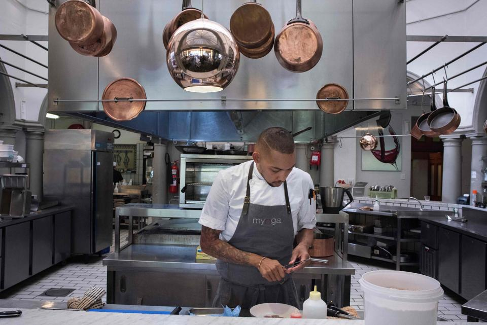 """Germaine Esau, Chef de cuisine at the Myoga fine-dining restaurant, uses Baleni salt to prepare a dish of seared tuna, preserved plum Eugenia berries, shiso, radish and macadamia in Cape Town. """"It's like nothing you've tasted before,"""" he says. """"It brings all the flavours out and just lifts everything,"""" he adds. (Michele Spatari / AFP)"""