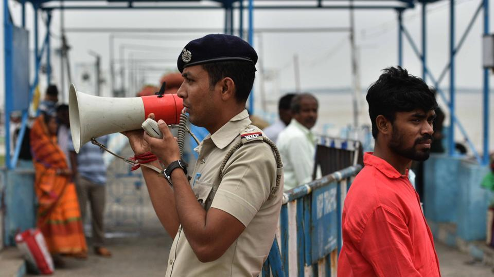"A police personnel makes an announcement on a loudspeaker for Cyclone Bulbul, at Harwood point jetty, South 24 Parganas. The India Meteorological Department said that Bulbul took around four hours to cover the Sunderbans spread across North 24 Parganas districts. In all, eight people have lost their lives in the state. ""Initial reports say 3,500 houses have been damaged,"" said North 24 Parganas district magistrate Chaitali Chakraborti. (Samir Jana / HT Photo)"