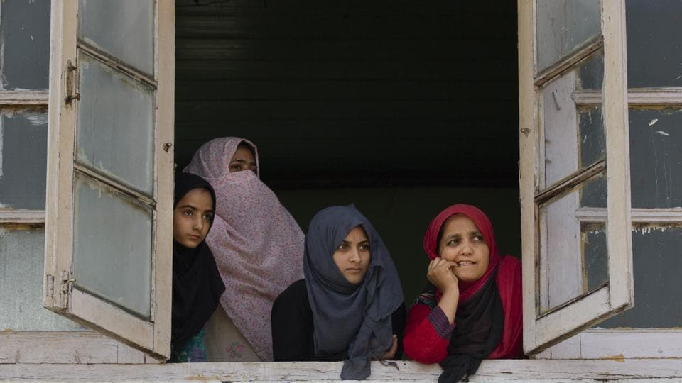 Kashmiri women watch a protest rally from the window of a mosque in Srinagar. While men historically make up most protesters and insurgents in the region and are often the first arrested or physically abused in security crackdowns, experts say Kashmiri women are suffering from the lockdown in their own less visible way. (Dar Yasin / AP)