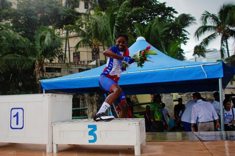 """Ousline Georges, 22, a member of the Haiti national cycling team, jumps down from the podium after receiving a bronze medal for the individual time trial under 23 category at the Caribbean Cycling Championship in Havana, Cuba. """"I was really moved,"""" said Georges, a student and mother of a four-year old boy. """"When I saw the others cry over my victory, I cried too."""" (Alexandre Meneghini / REUTERS)"""