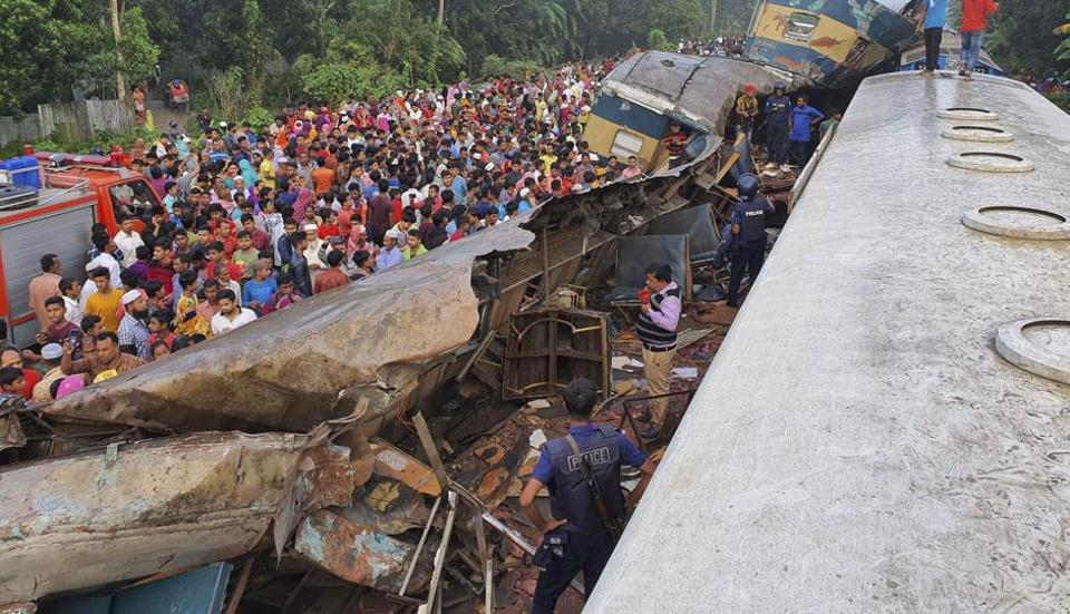 People gather near badly damages coaches after two speeding trains collided, east of the capital, Dhaka, Bangladesh, Tuesday, Nov.12, 2019.