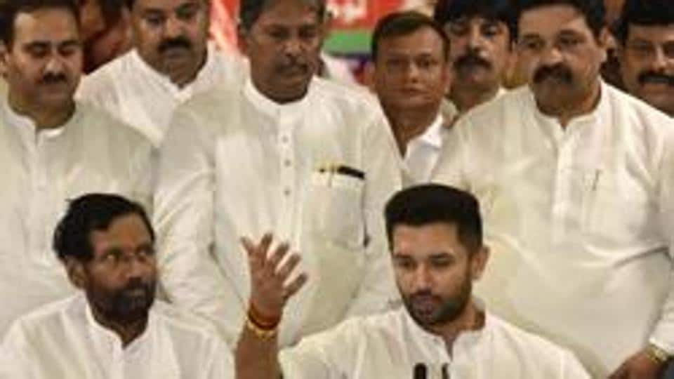 LJP leader Ram Villas Paswan looks on as his son Chirag Paswan who was appointed the new LJP chief addresses the media.
