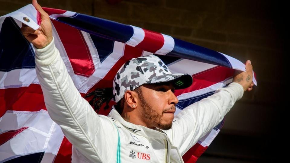 Lewis Hamilton  of Great Britain holds up the Union Jack.