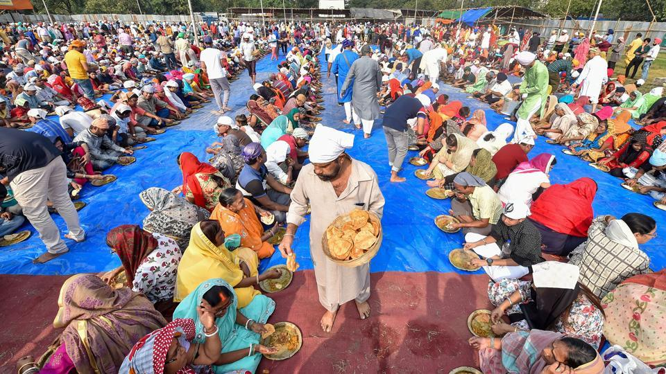 "Free meal is being served among the devotees on the occasion of 550th birth anniversary of Sikh Guru Nanak Dev, at Shahid Minar Maidan in Kolkata. ""Modi government is devoted to the thoughts and teachings of Guru Nanak Dev Ji, this is our prime motto of Sabka Saath, Sabka Vikas. The historic 'Kartarpur Corridor' dedicated to the countrymen by Modi ji on the 550th Prakash Parv of Guru Nanak Dev Ji is a real tribute to Guru Nanak Dev Ji,"" Union Home Minister Amit Shah said in a tweet. (Swapan Mahapatra / PTI)"