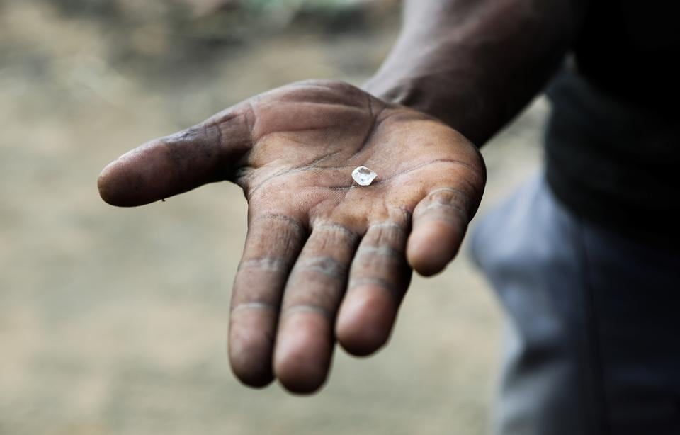 A miner holds an uncut diamond in his hand. Ekapa and Petra Diamonds PDL.L, then a part-owner of the mine, launched the initiative last year at Kimberley, hoping to address the problem. As much as 6 million rands' ($400,300) worth of diamonds were being taken by illegal miners each month, Ekapa estimates. In a bid to stem that, the company formed 836 miners and gave them a licence to mine the fields.  (Sumaya Hisham / REUTERS)