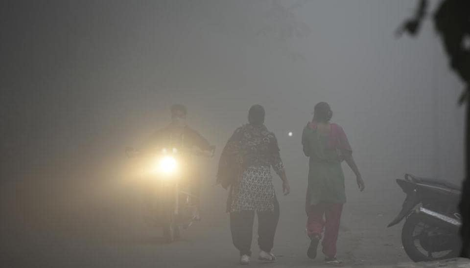People walk through smog and low visibility on Wednesday morning in New Delhi as air quality once again dipped to 'severe' category.