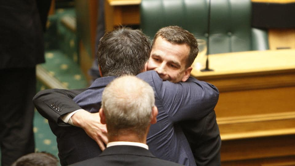 Euthanasia bill sponsor David Seymour, rear right, embraces other lawmakers at Parliament in Wellington, New Zealand.
