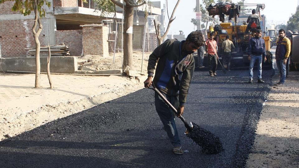 A worker at the construction site of the first plastic road in the city, at Sector 51, in Gurugram.