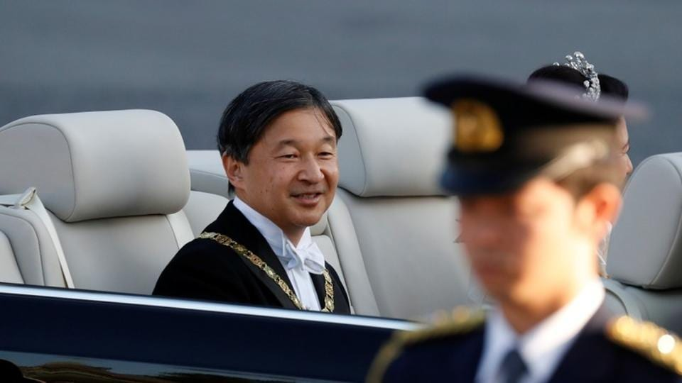 Japan's Emperor Naruhito and Empress Masako ride in a car during their royal parade to mark the enthronement of Japanese Emperor Naruhito in Tokyo.