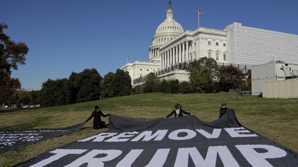 Demonstrators kneel near large banners on the lawn adjacent to the U.S. Capitol, while a top U.S. diplomat in Ukraine William Taylor, and career Foreign Service officer George Kent, testify before the House Intelligence Committee on Capitol Hill in Washington, Wednesday, November 13.