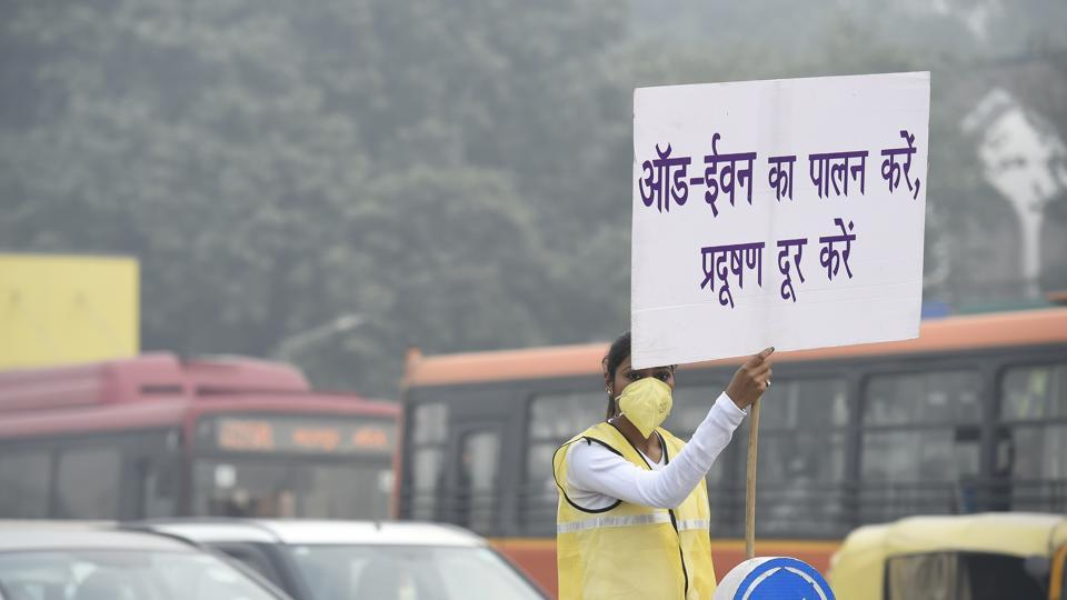 A civil defence personnel holds a placard to encourage commuters to follow the odd-even scheme, at ITO crossing, New Delhi, Ion Thursday, November 14, 2019.