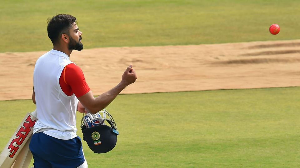 Indian cricket captain Virat Kohli throws the new pink ball.