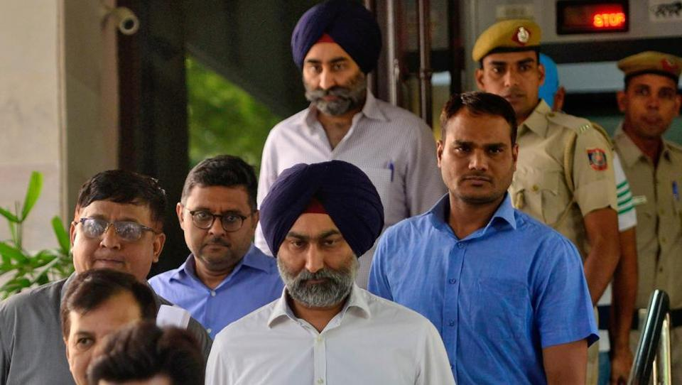 Police escort Malvinder Singh and his brother Shivinder Singh, former directors of Ranbaxy Laboratories, inside a court premises in New Delhi, India, October 11, 2019.