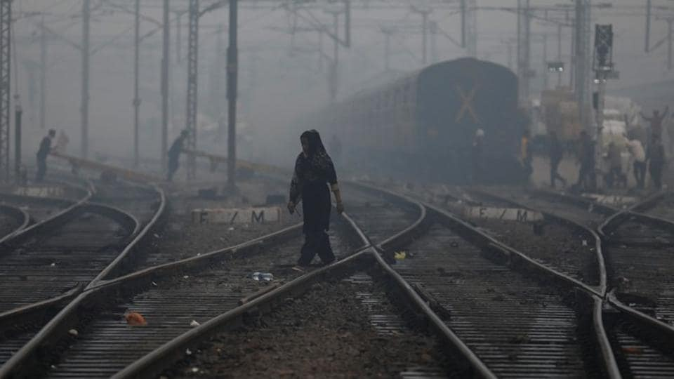 A woman crosses a railway line on a smoggy morning in New Delhi, India, November 15, 2019.