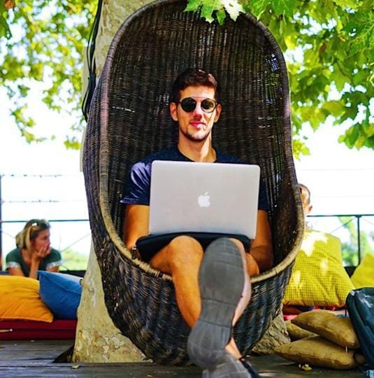Remote web developer Renato de Leão works at a garden cafe on a trip to Belgrade with Hacker Paradise. 'They provided a stable work environment through my working holiday,' he says.