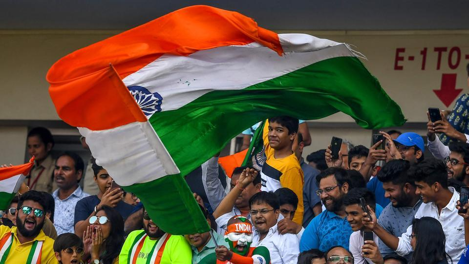 A cricket fan (C) waves the national flag during the third day of the first Test between India and Bangladesh at Holkar Cricket Stadium in Indore.
