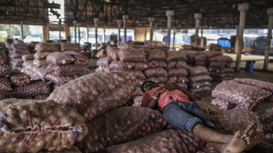 A worker sleeps on sacks of onions at the Vashi Agricultural Produce Market Committee (APMC) wholesale market in Mumbai.