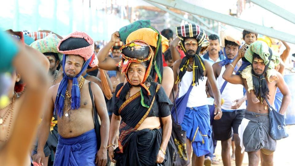 A woman is seen among the crowd of devotees at the Pamba base camp of Sabarimala Temple, in Pathanamthitta, Kerala. The Supreme Court on Thursday referred pleas seeking a review of its September 2018 order allowing the entry of women of all ages into Sabarimala Temple to a larger seven - judge without staying it, saying gender-based restrictions were not limited to the Kerala shrine but were also prevalent in places of worship of other religions. (Vivek R Nair/ HT Photo)