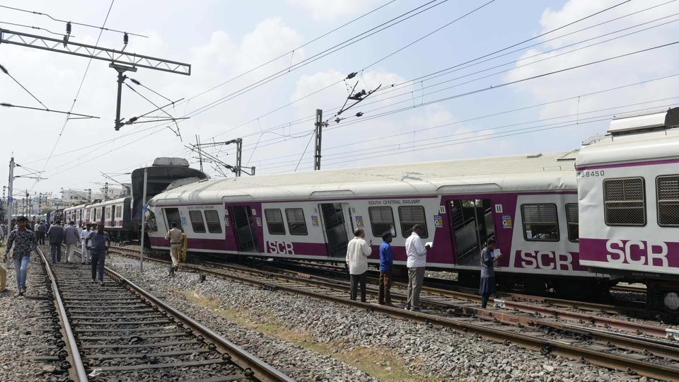 Railway workers and onlookers stand next to the askew carriages of a suburban rail train after it collided with an intercity express train at Kachiguda Railway Station in Hyderabad, Andhra Pradesh. Twelve people were injured in the accident.  (Noah Seelam / AFP)
