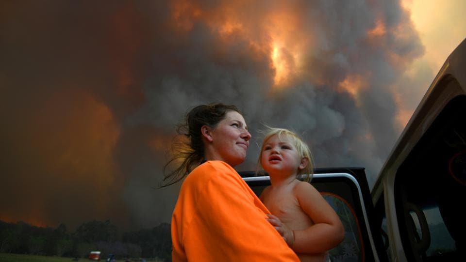 Sharnie Moren and her 18-month-old daughter Charlotte look on as thick smoke rises from bushfires near Nana Glen, near Coffs Harbour, Australia. The bushfire season has begun earlier than usual, in the southern hemisphere spring, and is expected to be long and brutal this year as a three-year drought has left broad swathes of Australia's east and west more susceptible to fire. (AAP Image/Dan Peled / REUTERS)