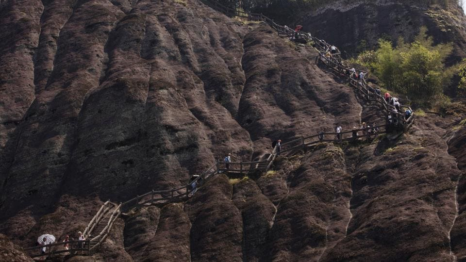 "Visitors climb Tianyou peak in Wuyishan, Fujian. ""It's quite urgent as soon as possible to identify the places, the ecosystems and other natural features"" to protect, Zhu says. Among other goals, China aims to build its own Yellowstone on the Tibetan plateau. (Ng Han Guan / AP)"