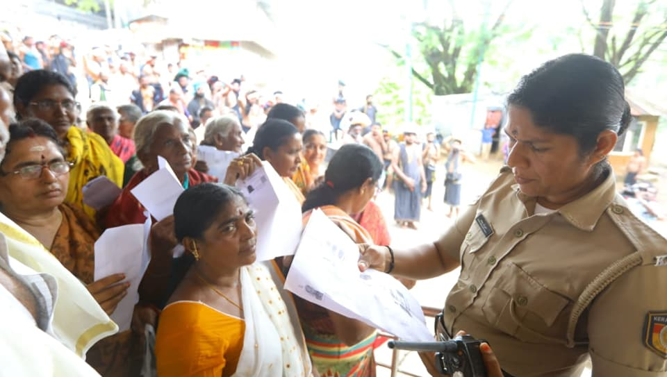 A police officer checking documents of women devotees to verify their age. Woman seen in yellow sari was later forced to retreat as she is 42, the barred age group.