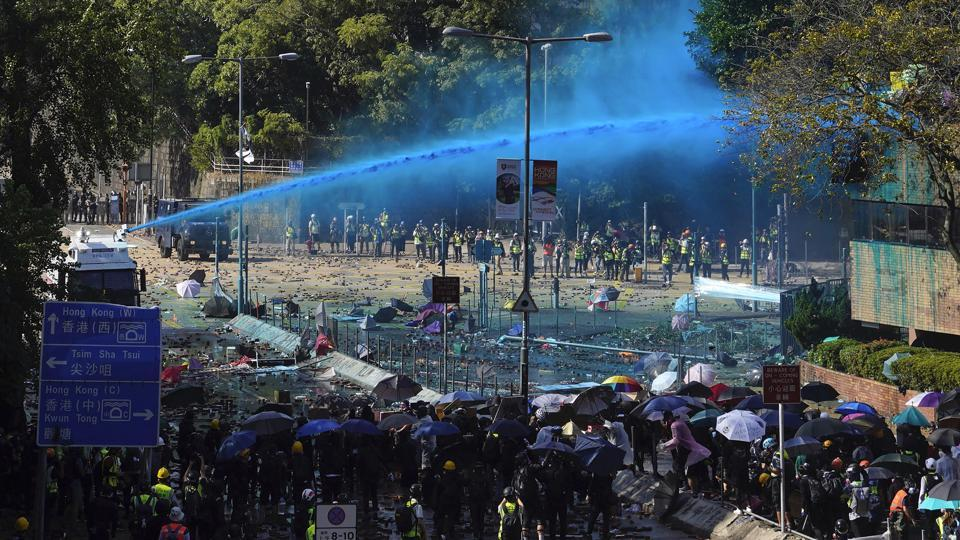 Police spray blue-dyed liquid from an armoured vehicle during a confrontation with protestors at the Hong Kong Polytechnic University in Hong Kong. A police officer was struck by an arrow fired by a Hong Kong protester on Sunday, as fierce clashes raged around a campus which has turned into a base for a pro-democracy movement switching tactics as it plunges the divided city deeper into turmoil. (Vincent Yu / AP)