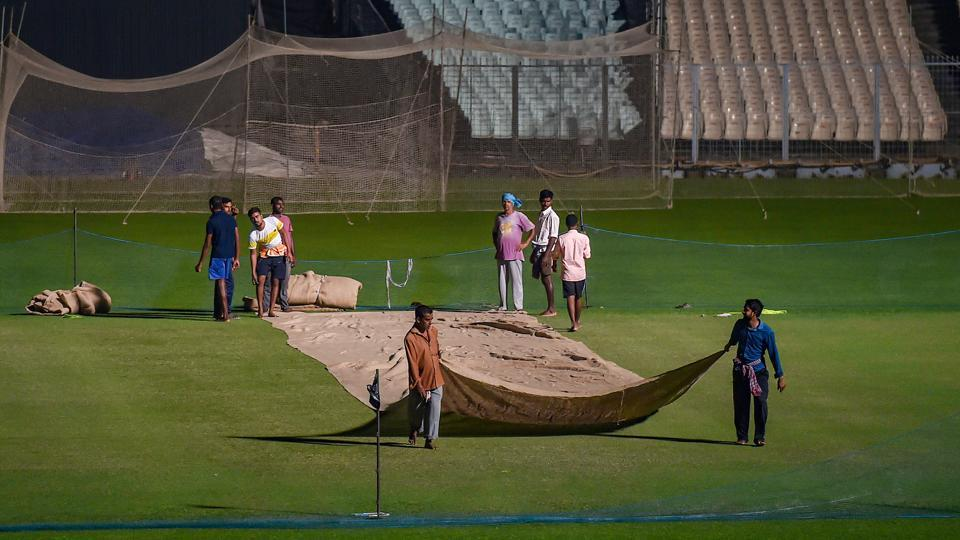 Groundkeepers cover the cricket pitch at Eden Garden to protect it from dew ahead of the first day-night Test match between India and Bangladesh.
