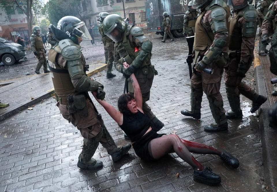 Riot police officers detain Camila Miranda after she was shot with 6 rubber bullets, 4 of which pierced her skin during a protest which she was demonstrating at against Chile's government in Santiago, Chile.  (Henry Romero / REUTERS)
