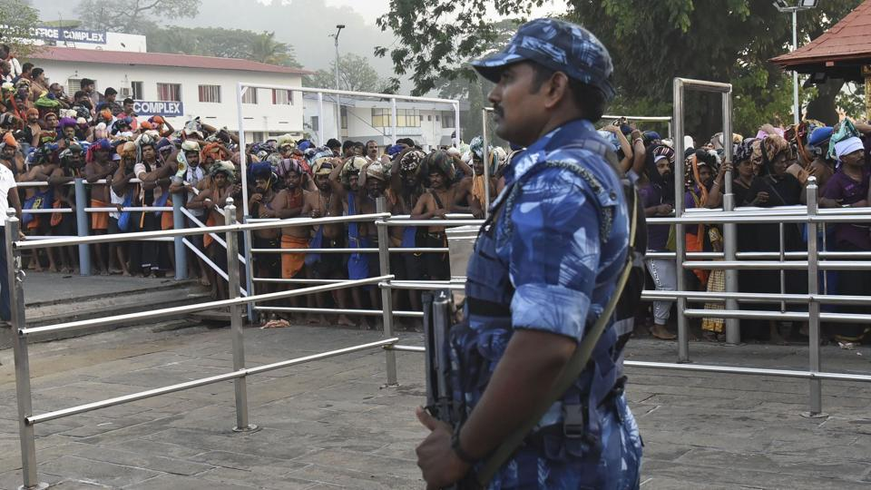 A Rapid Action Force jawan stands guard as devotees stand in queues to offer prayers at the Lord Ayyappa temple during the two-month long Mandala-Makaravillakku pilgrimage season, in Sabarimala, Monday.