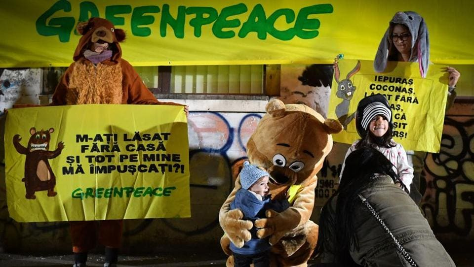 An activist dressed as bear hugs a child as another one (L) holds a placard reading