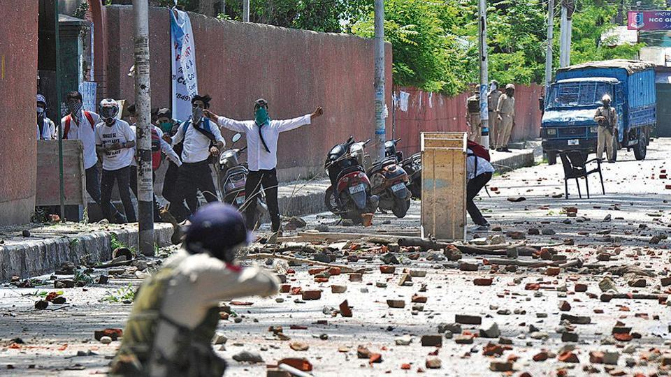 Students pelt stones during clashes with police personnel in Srinagar on May 14.