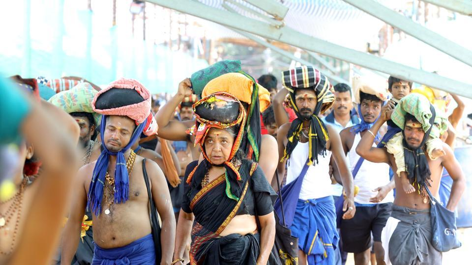 A woman is seen among the crowd of devotees at the Pamba base camp of Sabarimala Temple as the shrine opened for Mandala-Makaravilakku pooja in the evening at Pathanamthitta district of Kerala on Saturday.