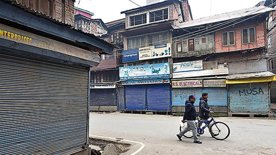 People walk past shops closed during a strike at Lal Chowk in Srinagar on Thursday.