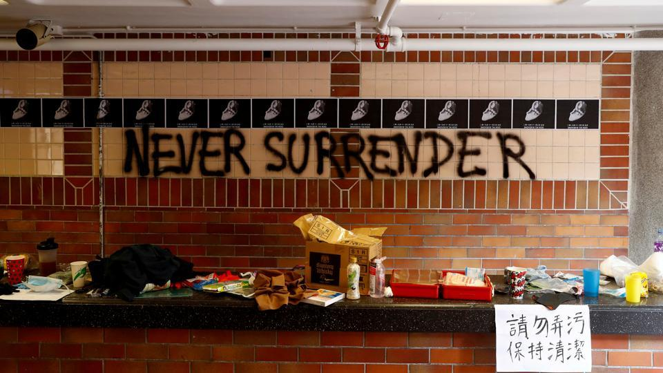 """The slogan """"Never Surrender"""" is spray painted on a wall in the besieged Hong Kong Polytechnic University (PolyU) in Hong Kong. Inside the increasingly empty and trashed campus of a Hong Kong university only a handful of activists held out on Thursday as they desperately searched for ways to escape or hide while squads of police encircled the grounds. (Thomas Peter / REUTERS)"""