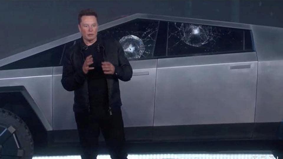Elon Musk stands in front of the cracked windows of Tesla Cybertruck.
