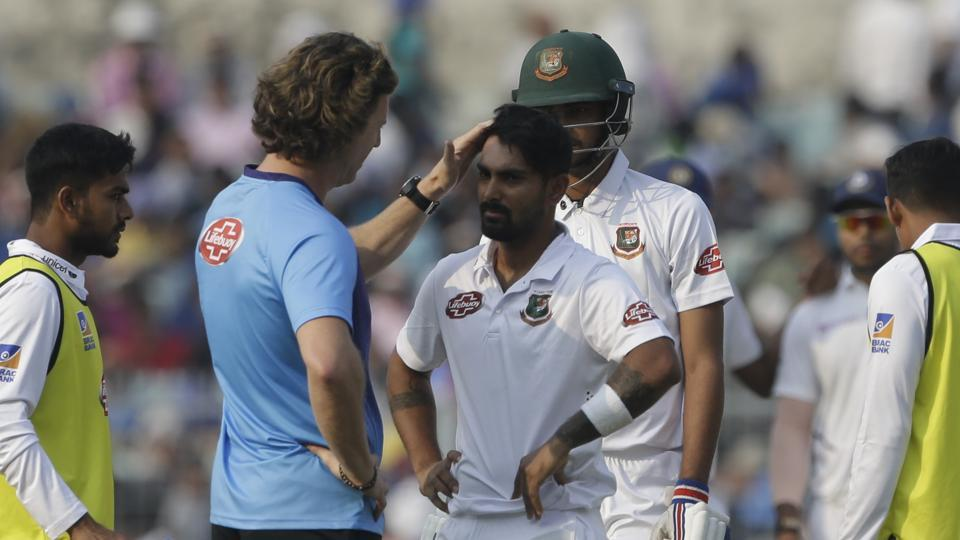 Bangladesh's team physio talks with Liton Das after he was injured by a delivery.