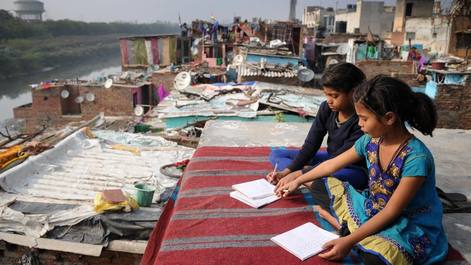 Poonam and Kiran, daughters of a cycle rickshaw puller, do their home work on the rooftop of their shanty in Noida.
