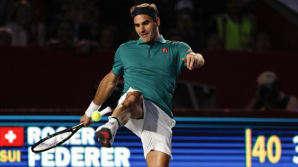 Roger Federer of Switzerland jokes around, juggling a tennis ball with his foot, during an exhibition match.