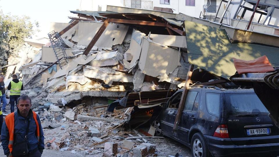 People stand next to a damaged building after a magnitude 6.4 earthquake in Durres, western Albania, Tuesday, Nov. 26, 2019.