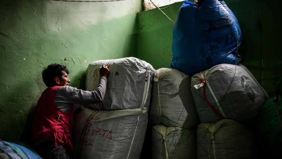 A man prepares to carry sacks of coca leaves at the coca market in La Paz. With a copy of the Bible in her hands, the right-wing senator took power after Morales quit on November 10 and fled to Mexico, where he was granted political asylum, after taking refuge in Chapare. (Ronaldo Schemidt / AFP)