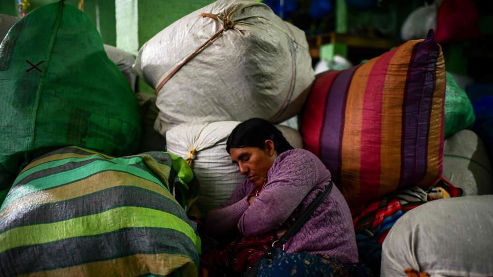 An indigenous woman rests on sacks of coca leaves at the coca market in La Paz. A socially fractured Bolivia took the first step into a future without Morales over the weekend with the annulment of the October 20 vote and the approval of new elections that exclude the former leader. (Ronaldo Schemidt / AFP)