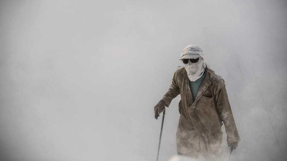 A labourer walks wearing protective gear at the 'White Mountain' limestone extraction quarry site near Egypt's southern city of Minya. Covered in fine white dust, labourers at this limestone quarry toil in brutal conditions with little workplace safety for paltry pay. (Khaled Desouki / AFP)