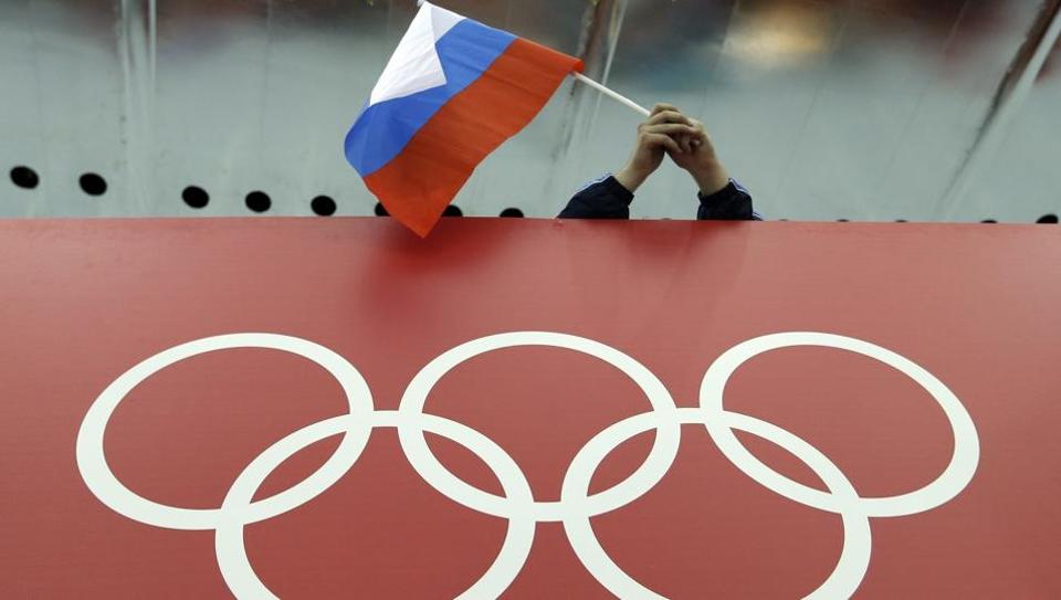 A Russian skating fan holds the country's national flag over the Olympic rings.