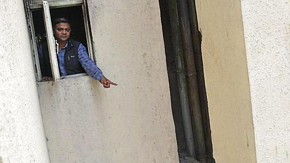 A man points to the beam on to which Rahul Singh had jumped to save himself from the fire on Tuesday morning.