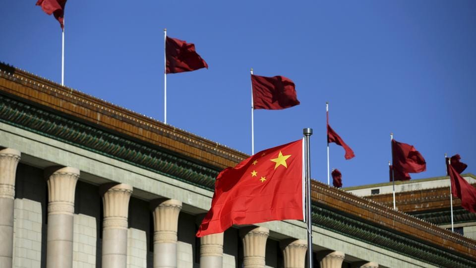 Chinese flag waves in front of the Great Hall of the People in Beijing.
