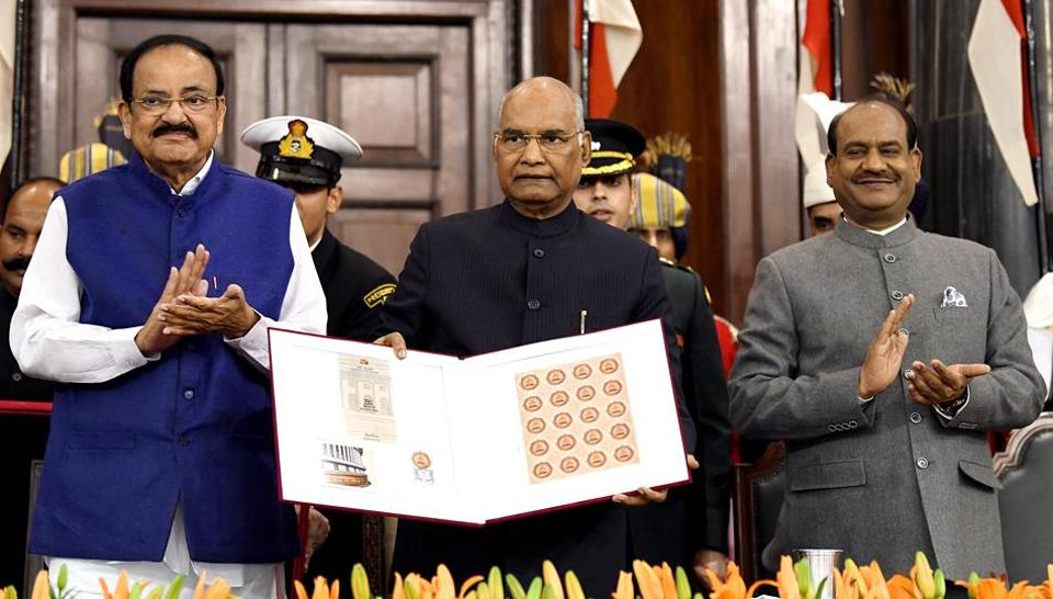 New Delhi, Nov 26 (ANI): President Ram Nath Kovind, Vice President M Venkaiah Naidu, and Lok Sabha speaker Om Birla releasing the commemoration postal stamp of the 250th session of Rajya Sabha during the joint sitting of parliament on the occasion of 70th Constitution Day celebrations, in New Delhi on Tuesday. (ANI Photo/ R Raveendran)