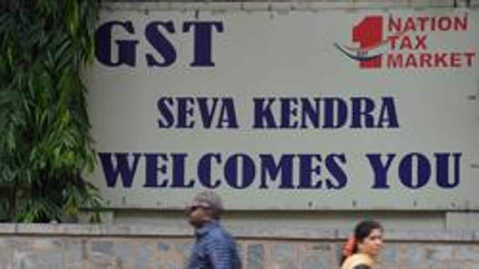 Indian pedestrians walk in front of a board advertising Goods and Service Tax (GST) in front of the Central Goods and Service Tax office in Bangalore.