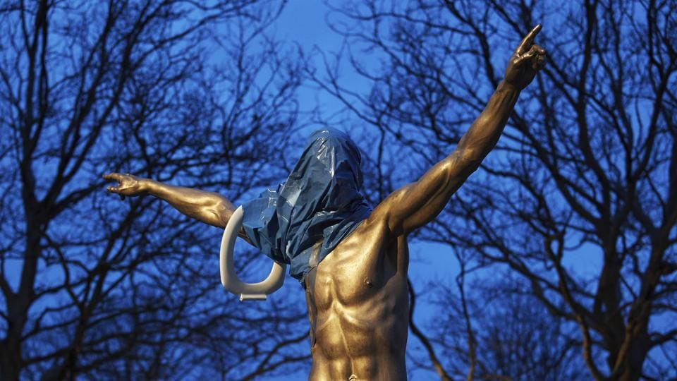 A blue plastic bag and a toilet seat hangs from the statue of the Swedish football player Zlatan Ibrahimovic in Malmo.
